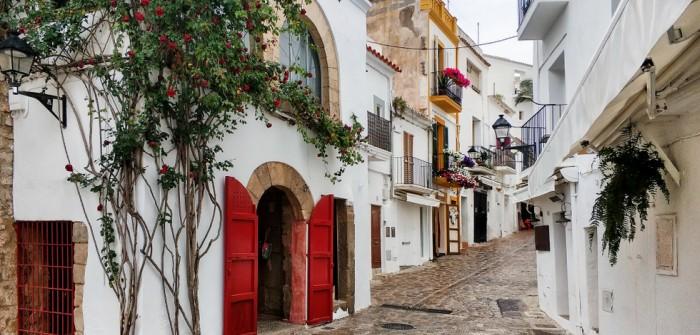 Das Glückshotel Ibiza kann führt auf eine Insel mit vielen überraschenden Facetten. Die Altstadt von Ibiza mit ihrem Kopfsteinpflasteer, den weißen Wänden ist oft sehr romantisch. Eivissa, wie die Katalanen das Kleinod nennen besticht auf diesem Foto mit pittoreskem Flair des Mittelmeers. Wuchernder Efeu, leuchtend rote Türen an weißen Häuserwänden - einfach eine malerische Altstadt.